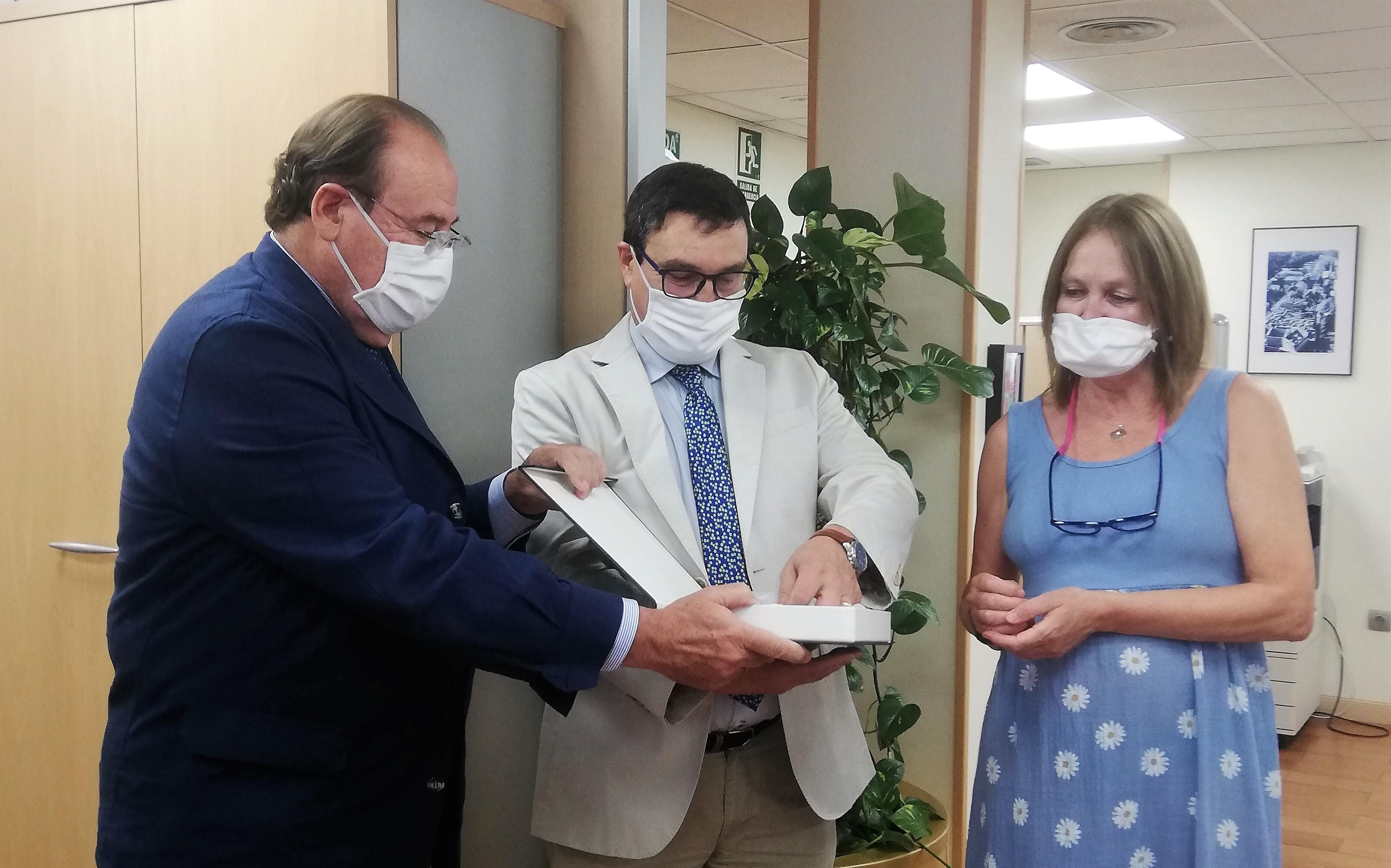 Pablo Pombo y Javier Orta entregando la placa de reconocimiento a la trabajadora Blanca Pérez